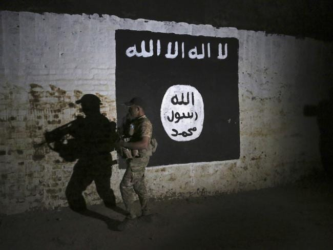 An Iraqi soldier inspects a recently-discovered train tunnel, adorned with an Islamic State group flag, that belonged to the former Baghdad to Mosul line, that was turned it to a training camp for IS fighters, in western Mosul, Iraq. Picture: Khalid Mohammed