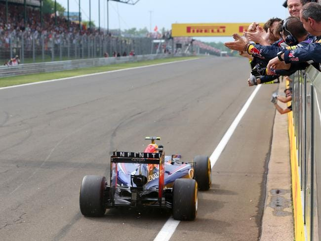 Daniel Ricciardo drives past members of his team in the pit straight at the Hungaroring. Picture: Getty Images