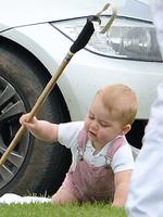 <p>Prince George raises his royal polo mallet as he watches his dad, the Duke of Cambridge and Prince Harry play in the Jerudong Polo Trophy at Cirencester Park Polo Club. Picture: Splash</p>