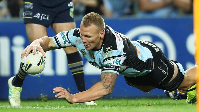 Luke Lewis reaches out to score a try for the Sharks. Picture: Brett Costello