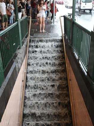 Water flows down to the subway on Flinders Street. Picture: David Crosling
