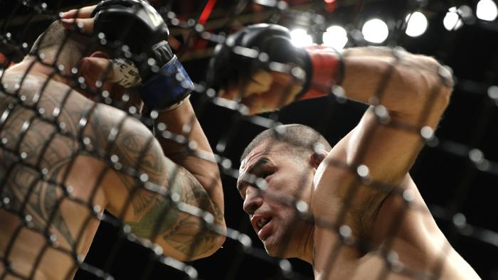 Cain Velasquez, right, hits Travis Browne.