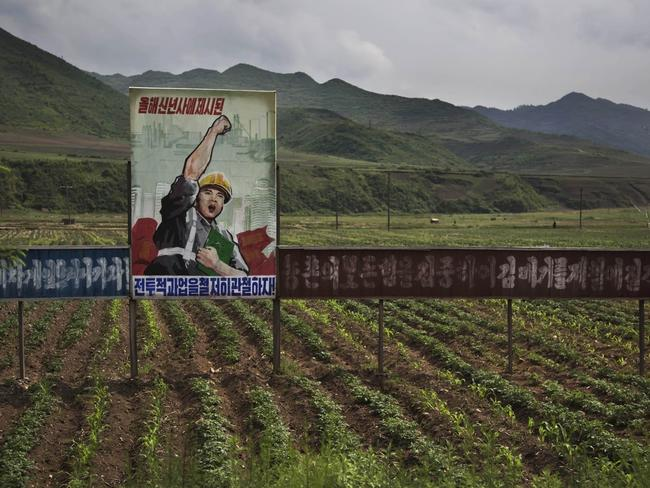 "A propaganda billboard stands in a field in North Korea's Ryanggang province. The sign reads: ""Let's complete the tasks set forth in the New Year's address."""