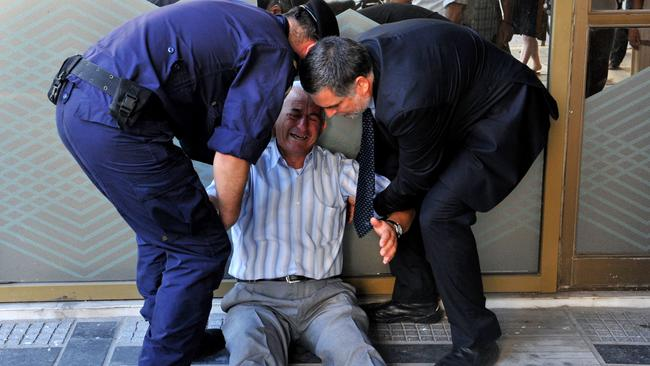 Giorgos Chatzifotiadis is assisted by an employee and a policeman as he sits on the ground outside a national bank branch, as pensioners queue to withdraw their pensions.
