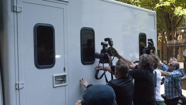 Leaving for prison ... photographers try to take a picture of the veteran entertainer Rolf Harris, at Southwark Crown Court in London. Picture: Bogdan Maran