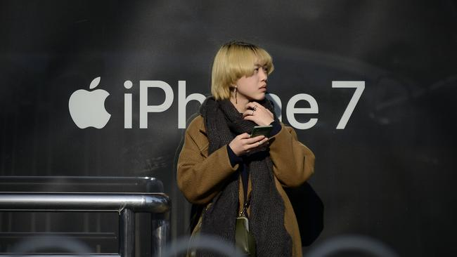 A woman looks on as she stands in front of a billboard promoting Apple's iPhone 7 at a bus stop in Beijing on 24 November 2016. Picture: Wang Zhao/AFP