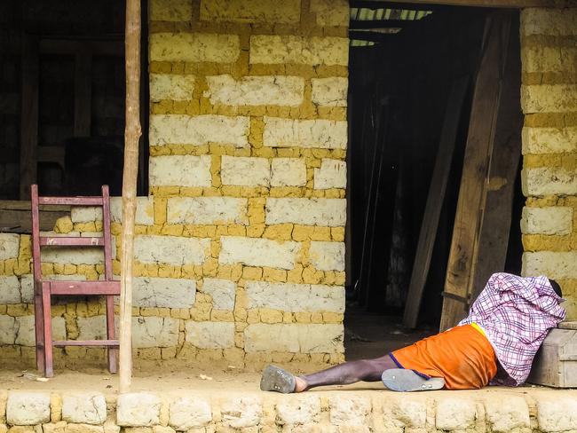 Suffering ... an Ebola victim lies outside a house in Port Loko Community, situated on the outskirts of Freetown, in Sierra Leone. Picture: AP