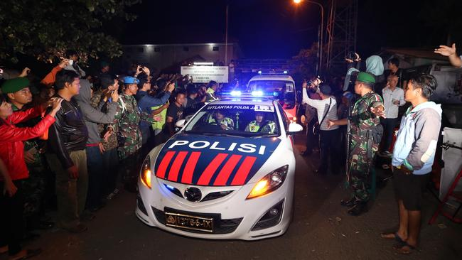 Repatriation begins ... A convoy of police and ambulance cars start the journey from Cilacap. Picture: Adam Taylor