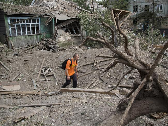 Devastation ... a man walks in a bomb crater near a damaged private house after the air strike in Snizhne. Picture: AP