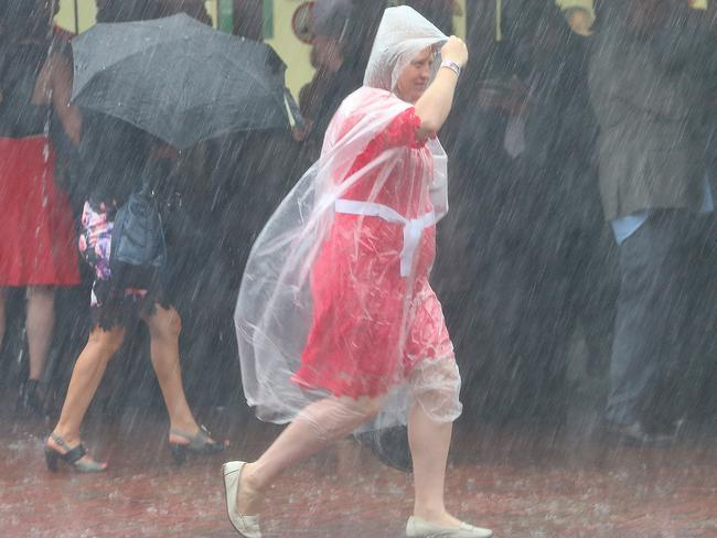 As the rain tumbles down, this woman raced to find shelter. Picture: Ian Currie