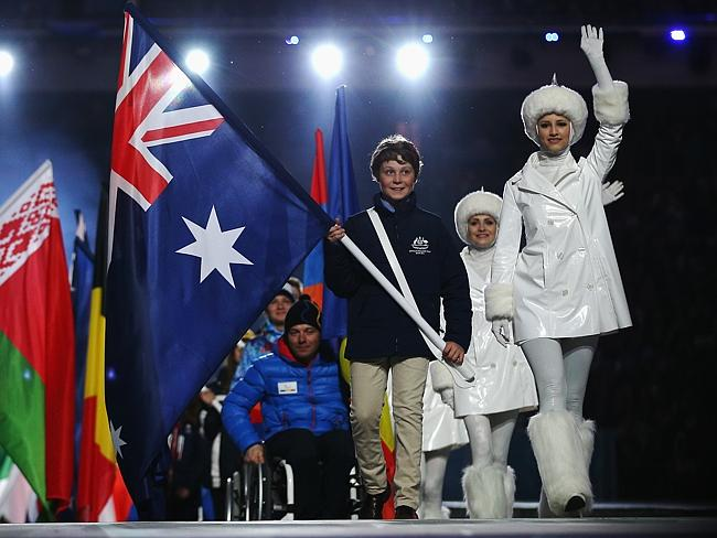 Flag-bearer and Alpine skier Ben Tudhope of Australia enters the stadium during the Sochi 2014 Paralympic Winter Games Closing Ceremony.