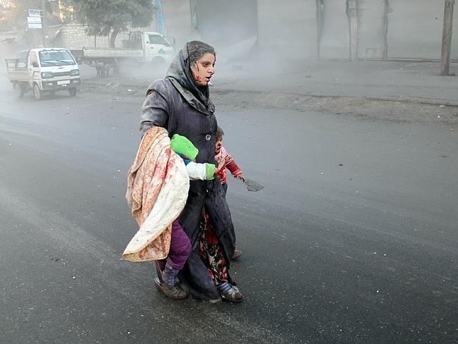 A wounded Syrian woman walks with her children following air strikes on a rebel area of the war-torn northern city of Aleppo on December 15, 2013.