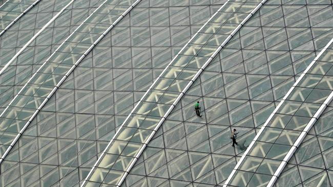 Workers clean the glass roof of the New Century Global Centre. Picture: AFP
