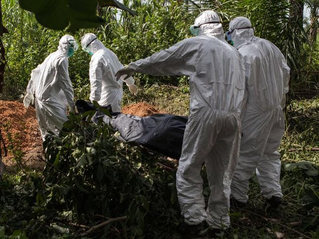 A specialised Ebola inhumation team carry the body of a recent victim to be buried in Magbonkoh, Sierra Leone.