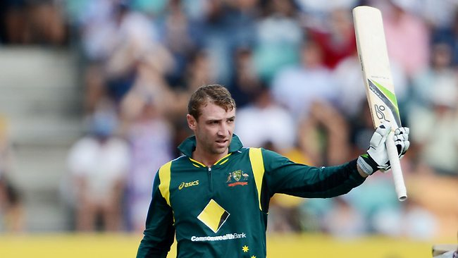 Phil Hughes raises his bat to the crowd after reaching his century.