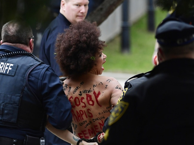 Police tackled the protester into bushes after she jumped the wall as Bill Cosby arrived at his sexual assault retrial. Photo: AP/Corey Perrine