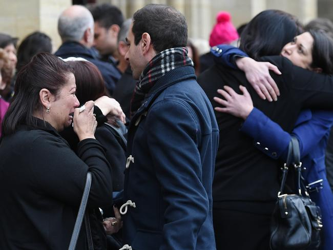 Family and friends of MH17 victims comfort each other outside the service. Picture: Jake Nowakowski