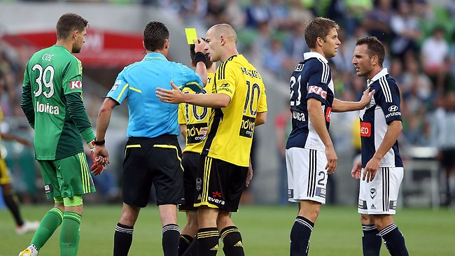 Stein Huysegems of the Wellington Phoenix talks to the umpire who gave teamate Louis Fenton a yellow card for faking a dive during the round 15 A-League match between the Melbourne Victory and Wellington Phoenix.
