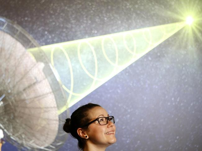 Emily Petroff, PhD candidate in Astrophysics, stands in front of an artist's impression of a Fast Radio Burst. Picture: Janine Eastgate