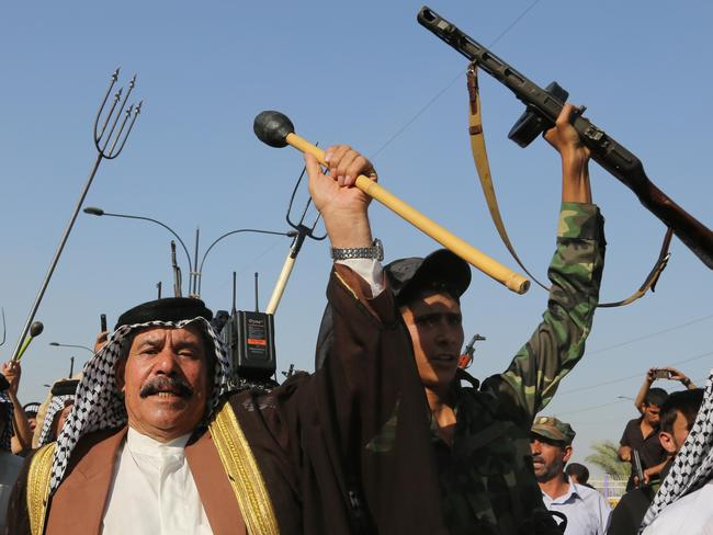 Pitchforks, clubs, Kalashnikovs ... Shiite tribal fighters raise their weapons and chant slogans against jihadist insurgents in the northwest Baghdad's Shula neighborhood, Iraq.