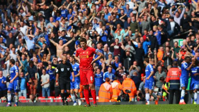 A dejected Steven Gerrard of Liverpool looks on as the Chelsea fans celebrate.