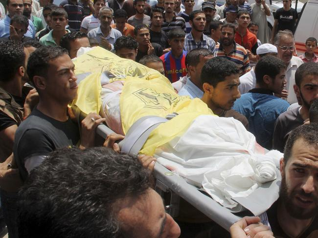 Victim ... Palestinians carry the body of Mohammed Abu Moamar, who was killed along with his brothers Hamza and Anas Abu Moamar during an air strike early Sunday. Picture: Hatem Ali