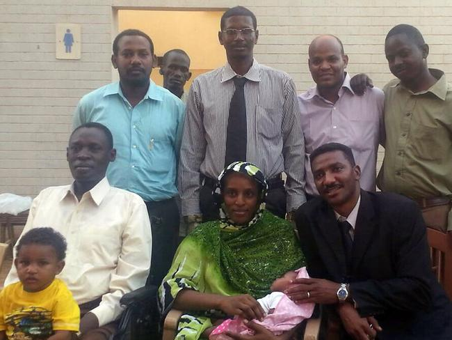 Rearrested ... Meriam Yahia Ibrahim Ishag (seated C), poses with her husband Daniel Wani (L) her newborn baby and the couple's 20-month-old son, as well as one of her lawyers Mohanad Mustafa (R), and other members of the legal team.