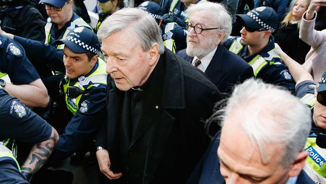 Cardinal Pell walks with a heavy Police outside court last year. Picture: Getty