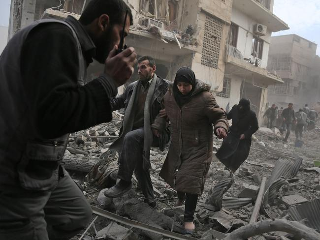 Civilians flee from an area hit by a regime air strike in the rebel-held town of Saqba. Picture: Abdulmonam Eassa/AFP