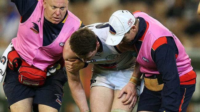 Patrick Dangerfield in the hands of Crows trainers.