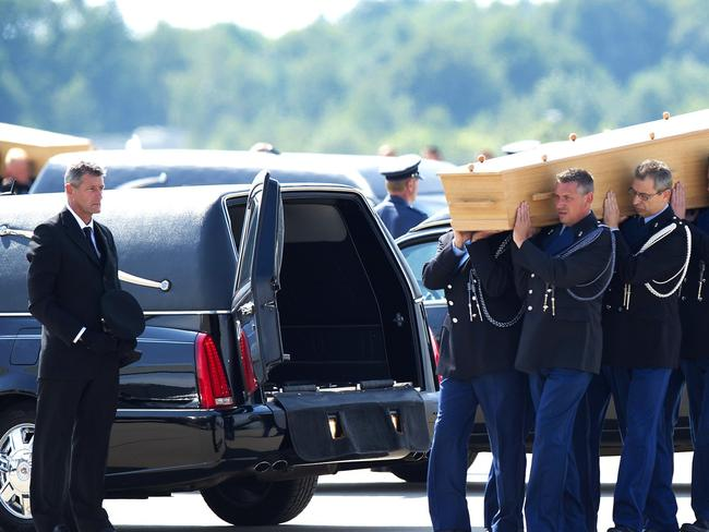 So many victims...Dutch military personnel carry a coffin to a waiting hearse at the airbase in Eindhoven after RAAF planes helped transport more remains of MH17 victims. Picture: AFP