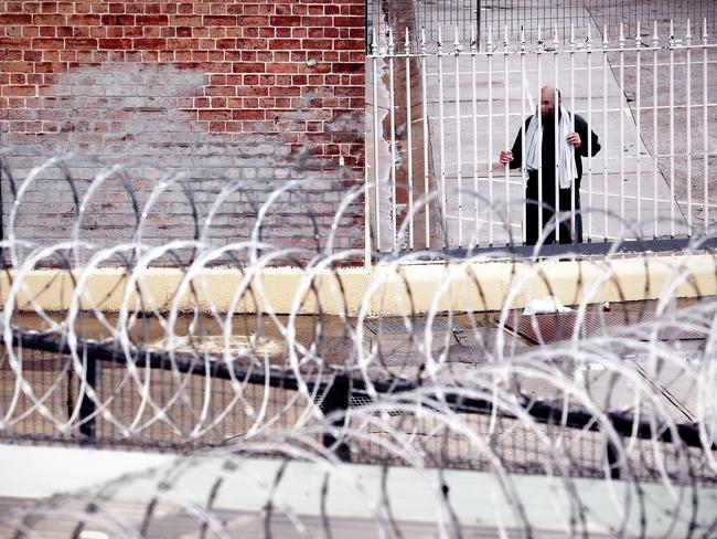 Razor wire fringes the walls above Goulburn main prison's yards where an inmate stands at a barrier. Picture: Sam Ruttyn.
