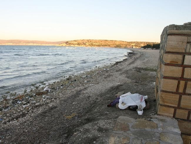 The little girl's body lies under a sheet on the Turkish coast. Picture: Stringer/Anadolu Agency/Getty Images