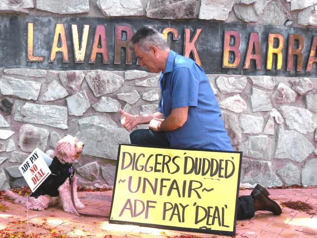 Protesting over effective pay cut ... Retired Colonel Ray Martin with Olly, the Activist Dog, outside the Army's Lavarack Barracks in Townsville.
