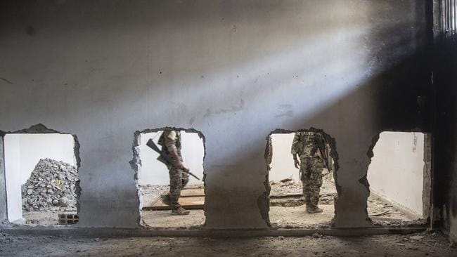Members of the US-backed Syrian Democratic Forces (SDF) walk inside the stadium that was the site of Islamic State fighters' last stand in the city of Raqqa, Syria. Picture: Asmaa Waguih