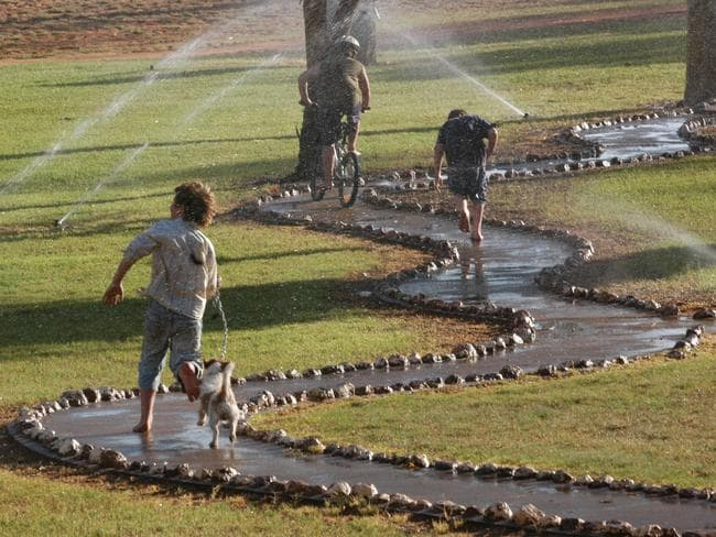 Charleville children running through the sprinklers at Graham Andrews Parklands. The State in the grip of a severe drought yet the township is drought proof due to the Great Artesian Basin. Photo: David Martinelli.