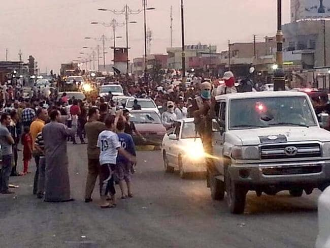 'Homecoming' parade ... jihadists parade down a main road in Mosul, Iraq. The predominantly Sunni north of Iraq has put up little resistance in the face of the mostly Sunni ISIS-led insurgency.