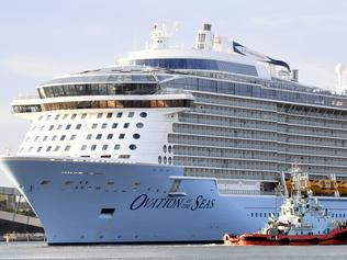 A tugboat is dwarfed by cruise ship Ovation of the Seas as she docks at the Port of Brisbane, Wednesday, Feb. 22, 2017. The $1.3 billion ship, owned by Royal Caribbean, is the largest cruise liner to operate out of Australia and the biggest to ever to visit the Port of Brisbane. The mega-liner is carrying more than 5000 passengers plus 1500 crew. (AAP Image/Dan Peled) NO ARCHIVING