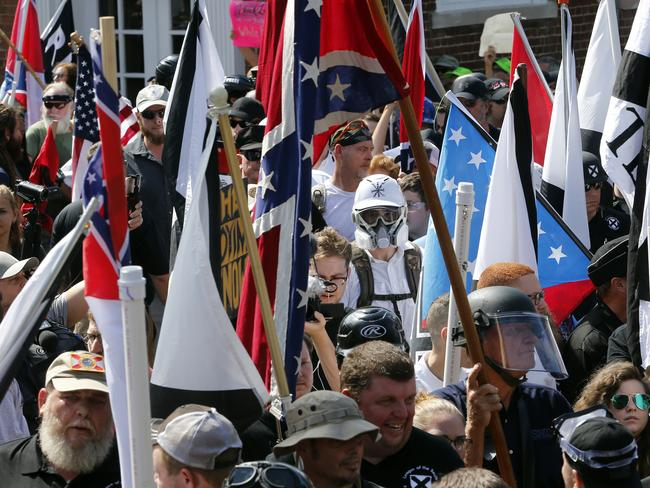 White nationalist demonstrators walk into the entrance of Lee Park surrounded by counter demonstrators in Charlottesville. Picture: AP