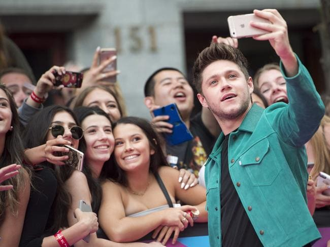 Niall Horan takes a selfie with fans. Picture: Nathan Denette/The Canadian Press via AP