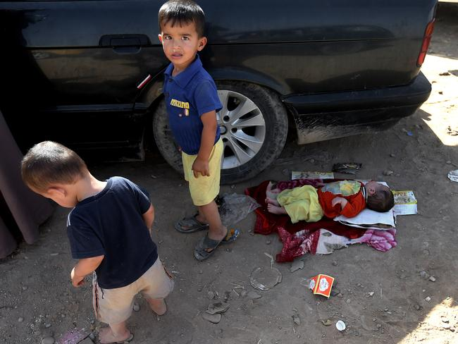 Iraqi children who fled their village with their family rest near their car outside of Mosul as they try to enter the Kurdish-controlled city of Irbil, in northern Iraq. Photo: Hussein Malla
