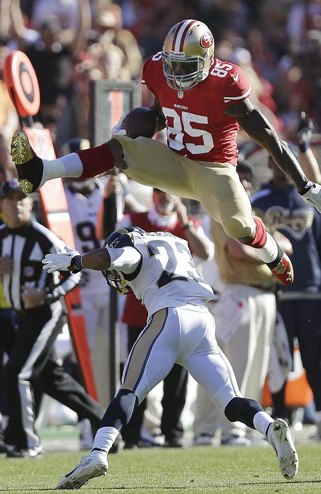 Vernon Davis jumps over St. Louis Rams free safety Rodney McLeod during a game in San Francisco.