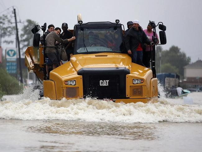 People catch a ride on a construction vehicle down a flooded street. Picture: Joe Raedle/Getty Images/AFP