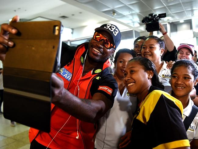 Chris Gayle poses for photographs with the PNG Womens Cricket Team