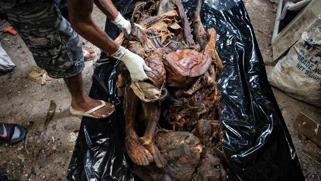 A worker arranging cadavers in various stages of decomposition at the morgue of Henry's Funeral Homes in Manila. Picture: AFP/ Noel Celis.