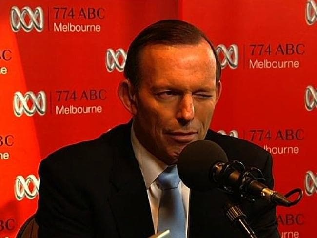 Prime Minister Tony Abbott winks to radio host Jon Faine while he takes questions from a caller who identified herself as a phone sex worker