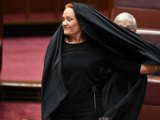 One Nation Senator Pauline Hanson takes off a burqa during Senate Question Time at Parliament House in Canberra. Picture: AAP/Lukas Coch