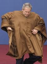 President George W. Bush struggles with his poncho.
