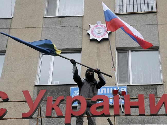 New order ... a masked pro-Russian man discards a Ukrainian flag after replacing it with a Russian flag on a ledge above a police station stormed by a mob in Gorlivka. Picture: AP