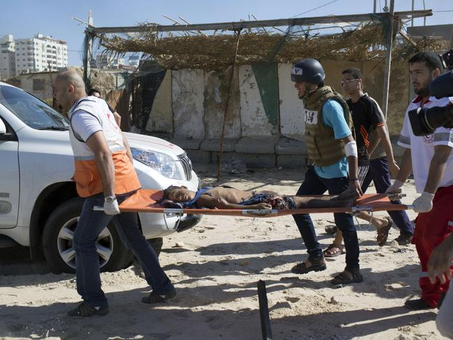Rescue workers carry one of the boys, all from the Bakr family, killed or injured on the beach during the Israeli bombardment of Gaza City. The shelling was witnessed by journalists. The strikes appeared to be the result of shelling by the Israeli navy against an area with small shacks used by fishermen.